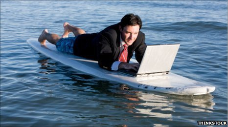 A digital nomad working on a surf board